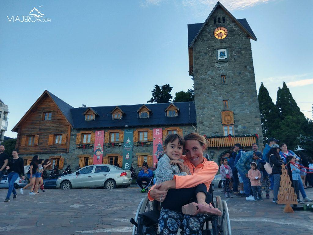 Naty sentada en la silla de ruedas con Sari en su falta y el Centro Civico de Bariloche de fondo