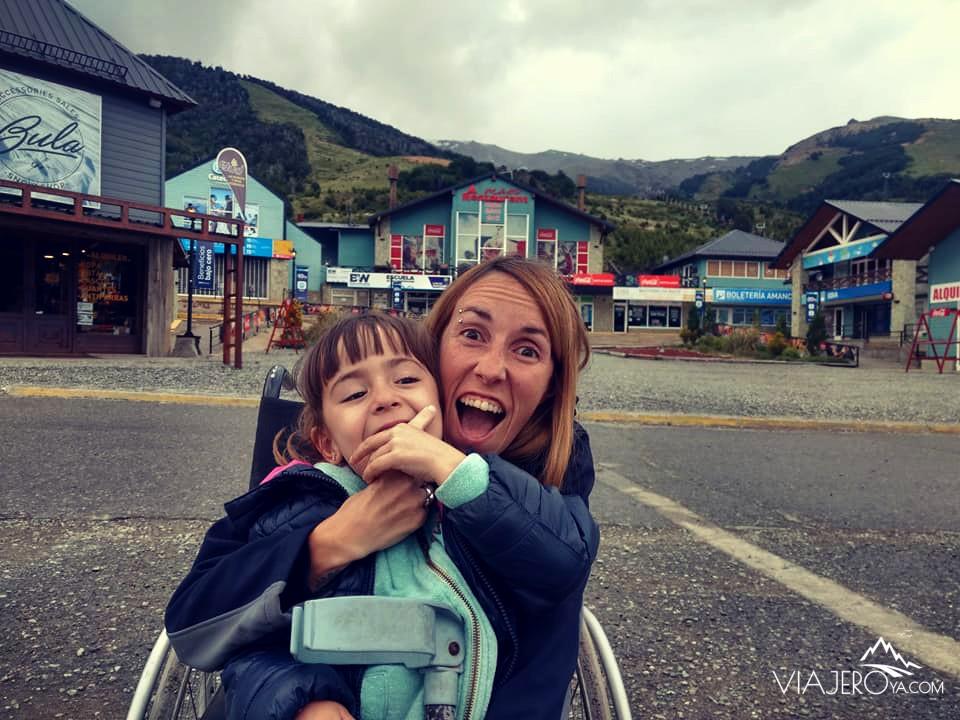 Naty sentada en la silla de ruedas y Sara mordiendo su dedo riendo con el Cerro Catedral de fondo