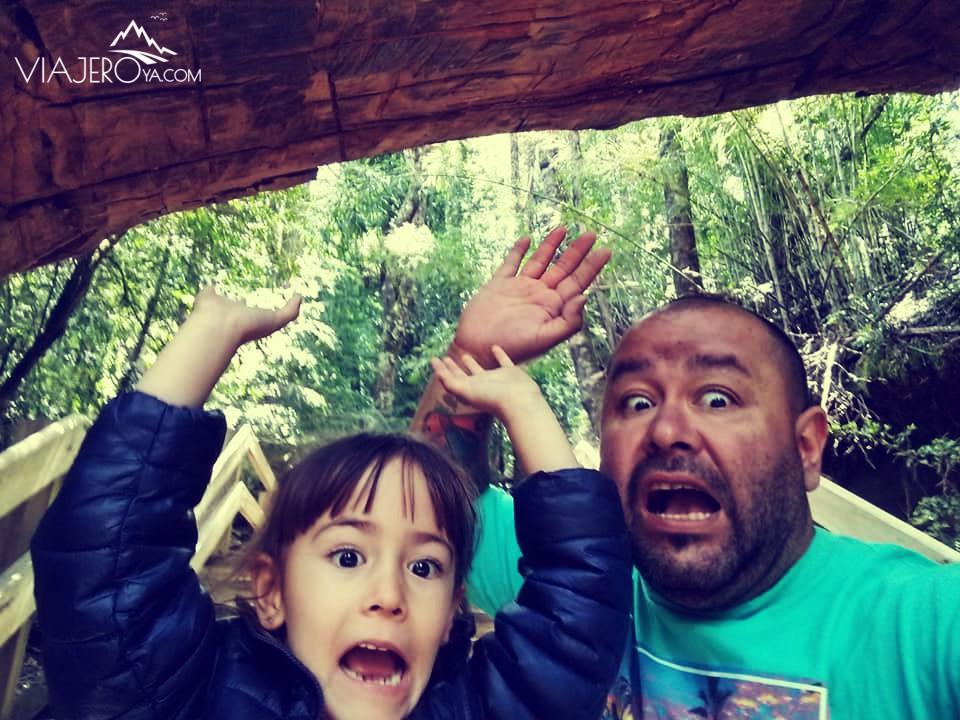 Sara y Edu con cara de asustados haciendo que un tronco se les cae en la cabeza